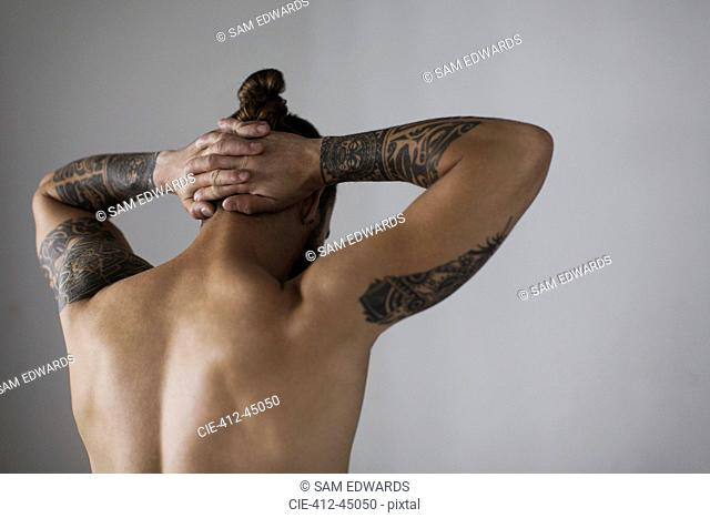 Rear view bare chested hipster man with tattoos
