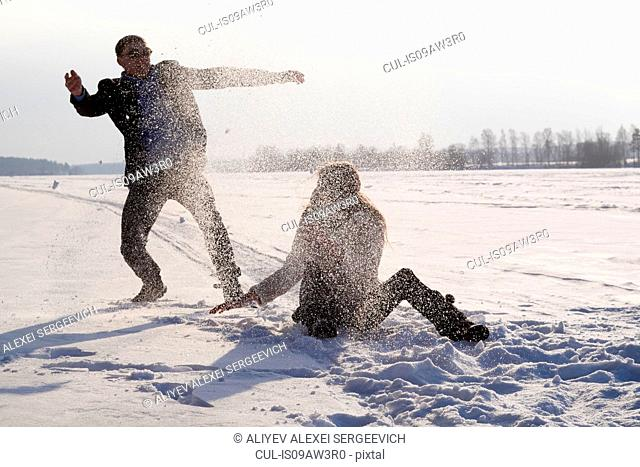Young couple playing on snow-covered field