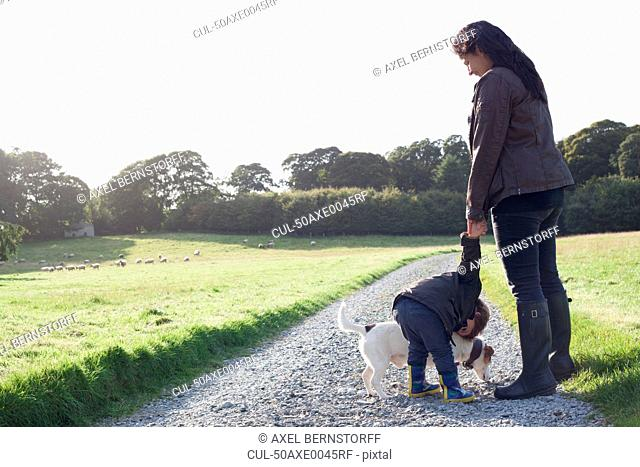 Mother and son walking dog on dirt road