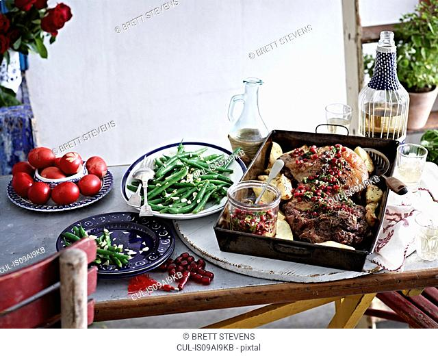 Still life of roasted lamb with pomegranate seeds and vegetables