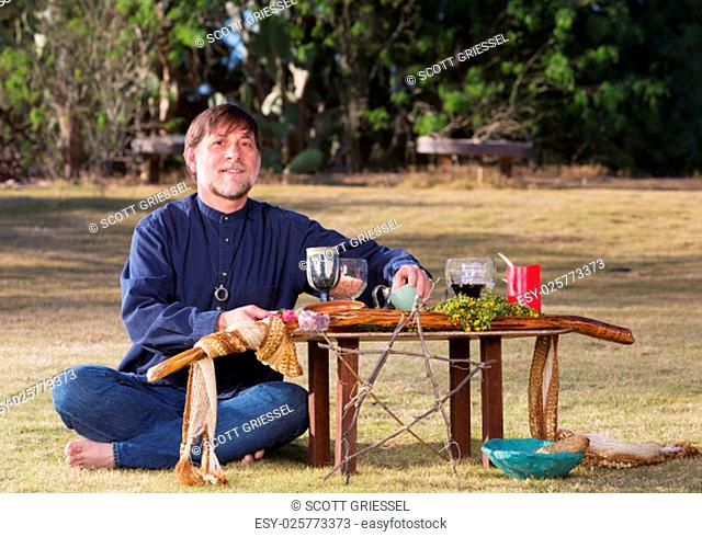 Single bare foot male at pagan altar outdoors