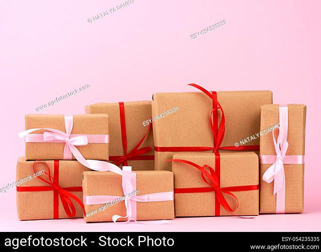 stack of gifts in boxes wrapped in brown kraft paper and tied with silk ribbon on a pink background. Festive concept, copy space