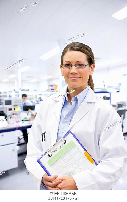 Female Engineer With Clipboard In Electronics Clean Room