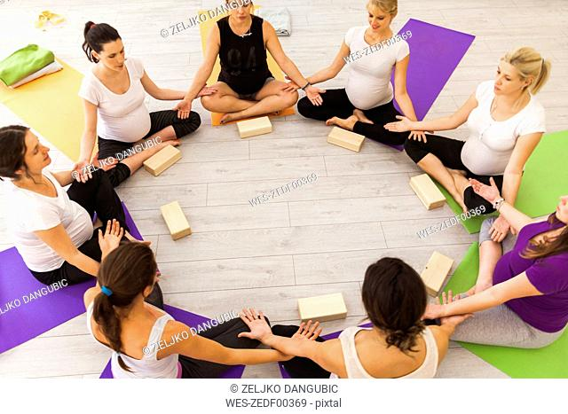 Prenatal yoga class sitting together in circle