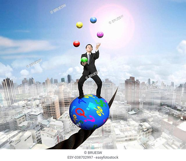 Juggling businessman standing on top of colorful symbols ball, balancing on a wire, with sun mist cityscape background