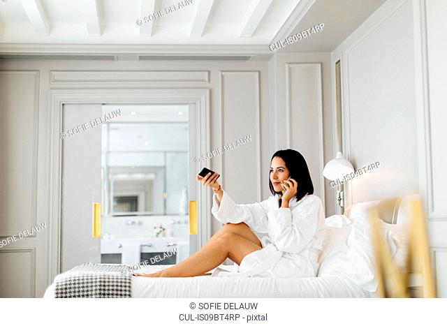 Woman using smartphone and remote control in suite