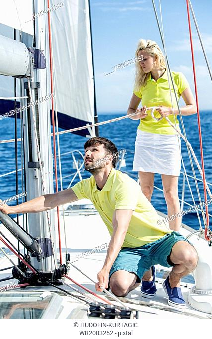 Young couple adjusting rigging on sailboat, Adriatic Sea