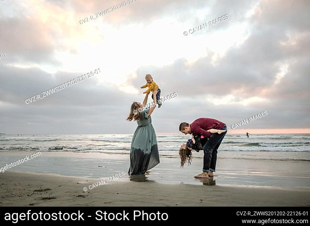 Young parents playing on the beach with children at sunset