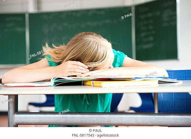 Exhausted teenage girl in classroom