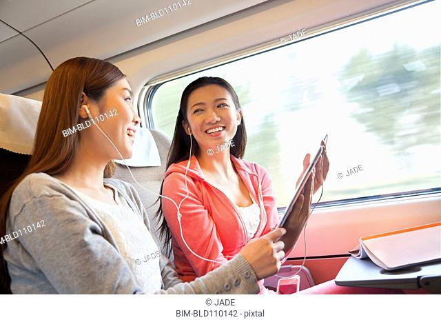 Chinese women listening to headphones on train