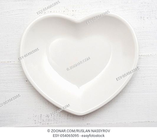 Heart shaped plate on a wooden background