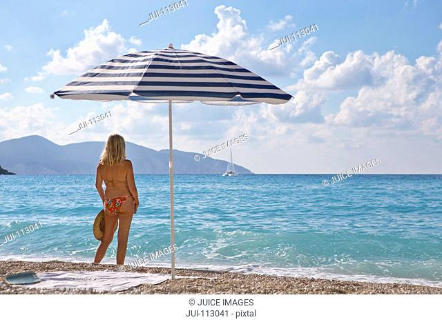 Woman standing on sunny beach looking at ocean view near beach umbrella