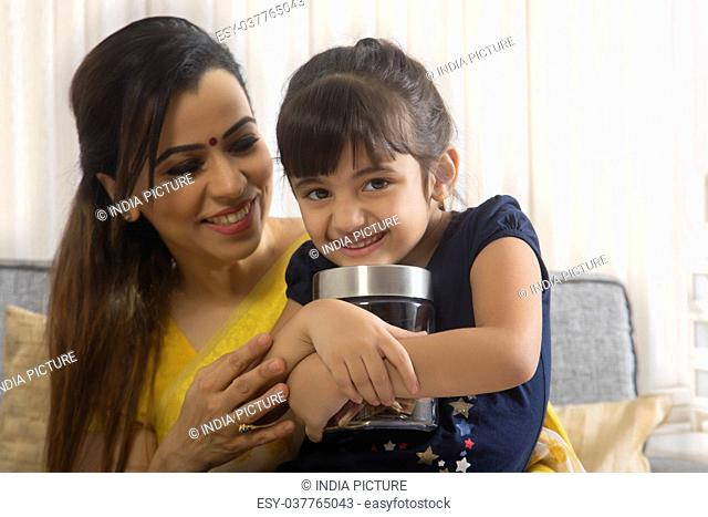 Smiling mother and daughter holding coin box