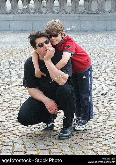 Boy and kneeling man both wearing black sunglasses hug on the fan shaped cobbles in front of an elipical stone balustrade in Belgium