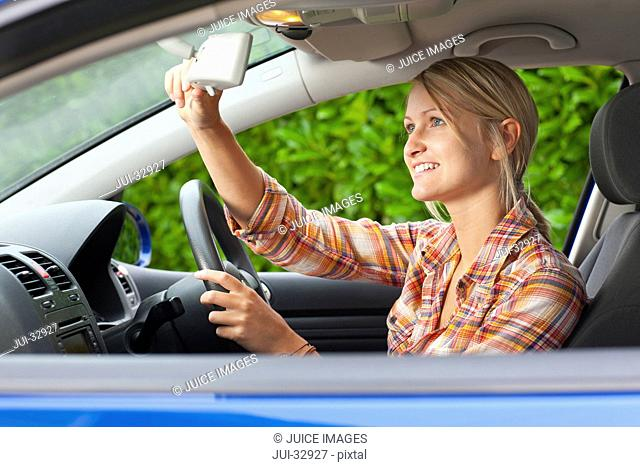 Smiling woman driving car and adjusting rear-view mirror