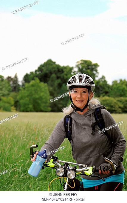 Older woman riding bicycle on rural road