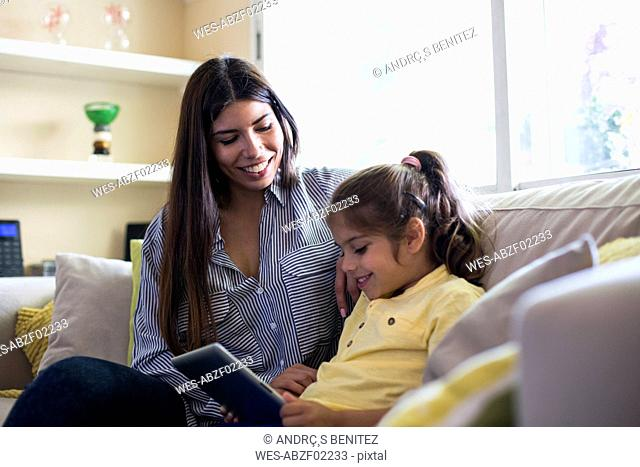 Happy mother and daughter sitting on couch at home using tablet