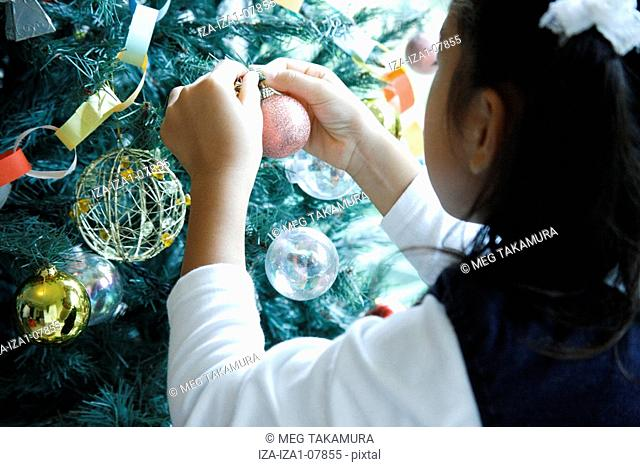 Rear view of a girl decorating a Christmas tree