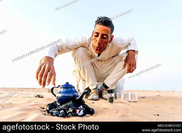 Man preparing tea in Sahara desert, Tindouf, Algeria