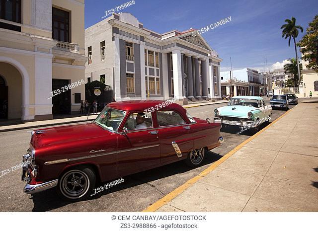 Old American cars in front of the Colegio San Lorenzo at Plaza De Armas, Cienfuegos, Cienfuegos Province, Cuba, Central America