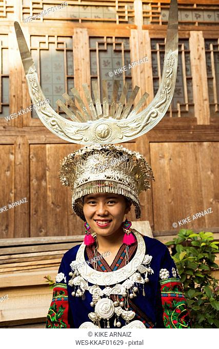 China, Guizhou, portrait of a young Miao woman wearing traditional dress and headdress