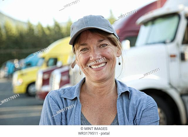 A Caucasian woman truck driver near her truck parked in a parking lot of a truck stop