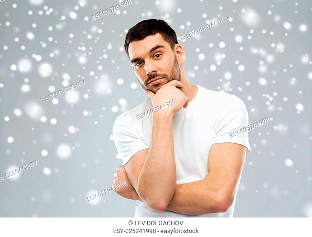 doubt, winter, christmas and people concept - man thinking over snow on gray background