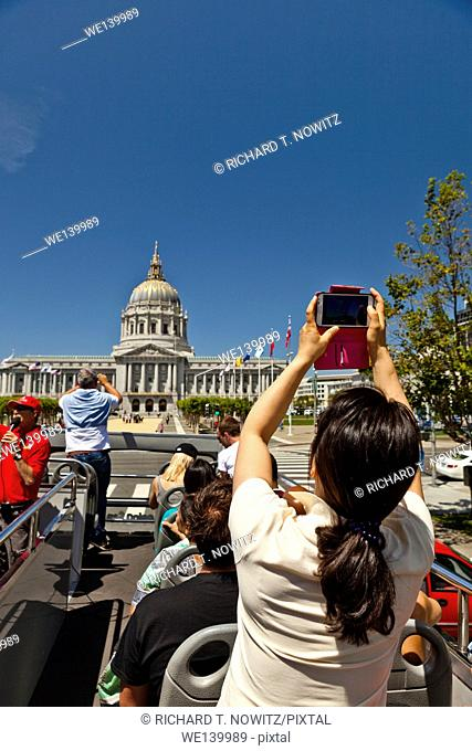 Tourist uses a smartphone to photograph the San Francisco City Hall Building from the deck of an open tour bus