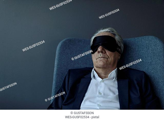 Senior businessman sitting in armchair wearing eye mask