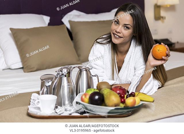 Charming brunette in white bathrobe lying on bed with plate of fruit and served tea on tray