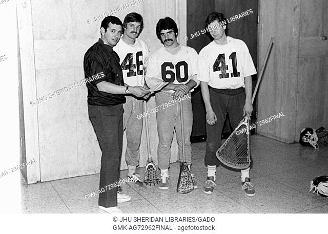 A full length portrait of a Johns Hopkins University lacrosse coach Henry Ciccarone discussing strategy with two lacrosse players and a goalie