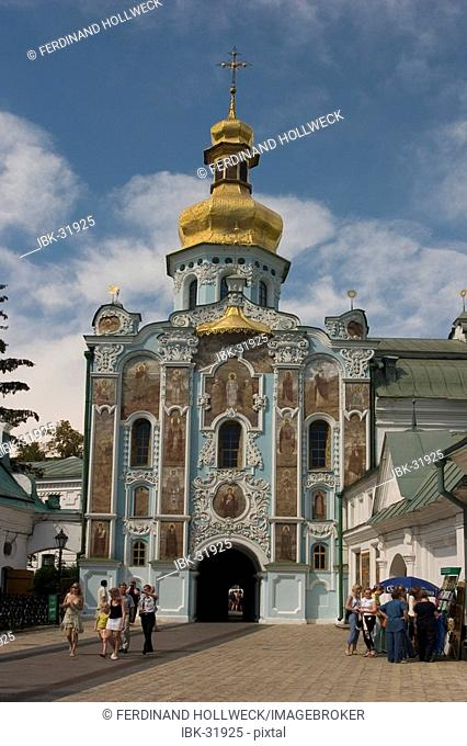 Ukraine Kiev the monastery of cave Kyjevo Pecers'ka Lavra view to the Trinity gate church pilgrims and people blue sky and clouds shining dome and cross of...