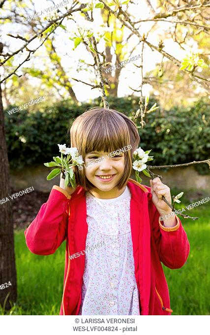 Portrait of smiling little girl holding twig of blossoming tree