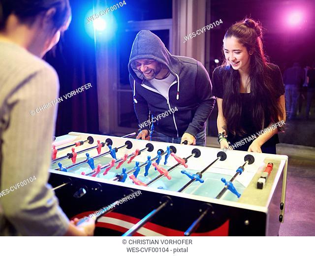 Happy friends playing foosball