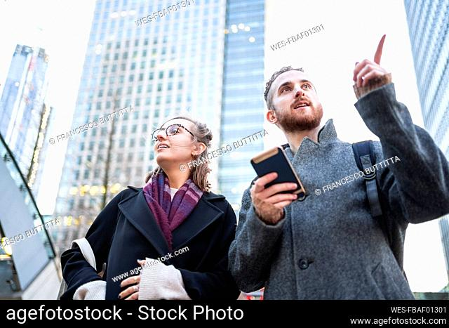 Young couple with cell phone in the city looking around, London, UK