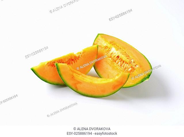 Slices of cantaloupe melon on white background