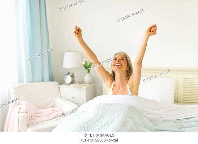 Senior woman stretching in bedroom in morning