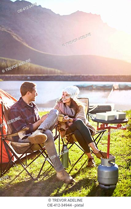 Young couple camping, drinking coffee at sunny lakeside campsite