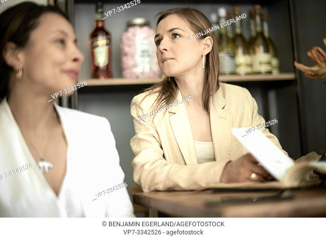 stylish woman searching for waiter to make a order in restaurant, in Munich, Germany