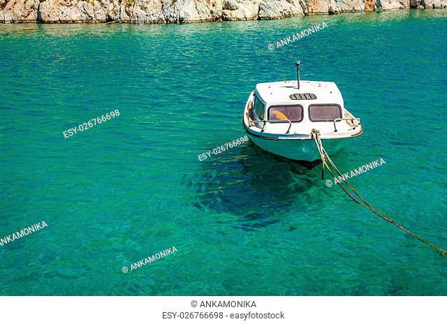 Small empty white motorboat moored in Greek sea bay