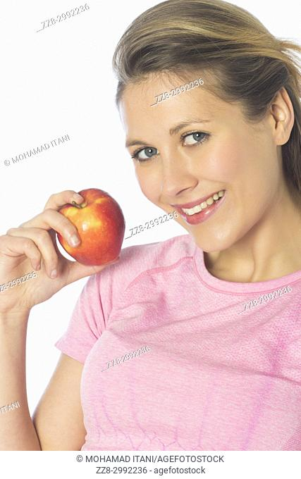 Beautiful blond woman holding a red apple against a white background