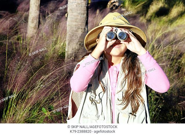 A young girl pretending to be on safari looking through binoculars