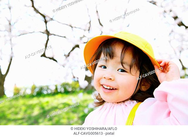 Young smiling Japanese girl enjoying cherry blossoms in a city park
