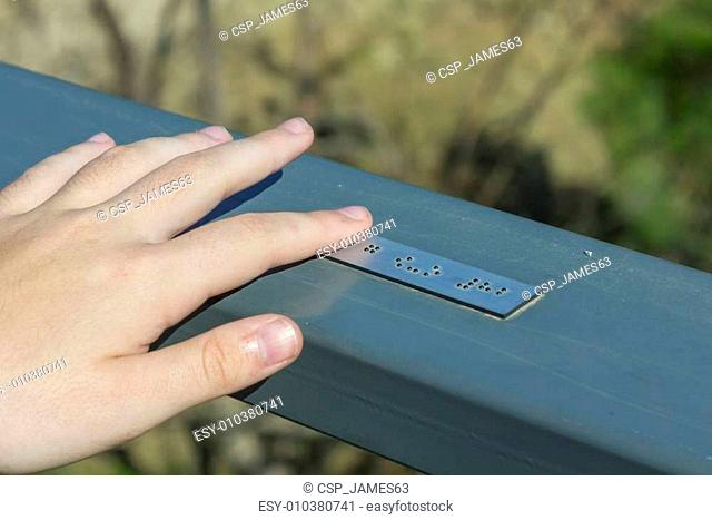 Young hand reading braille writing
