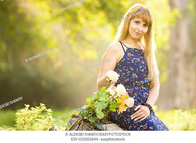 Beautiful young girl on the background of the sunny blurred greenery, lies next to a bouquet of roses