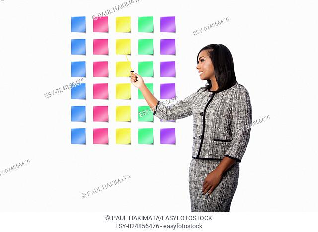 Beautiful happy smiling business woman presenting colorful blank sticky notes, on white