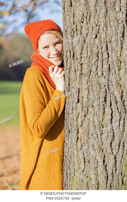 Pretty blonde woman leaning on a tree in park in autumn