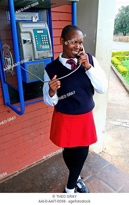 School girl using payphone, St Mark's School, Mbabane, Hhohho, Kingdom of Swaziland