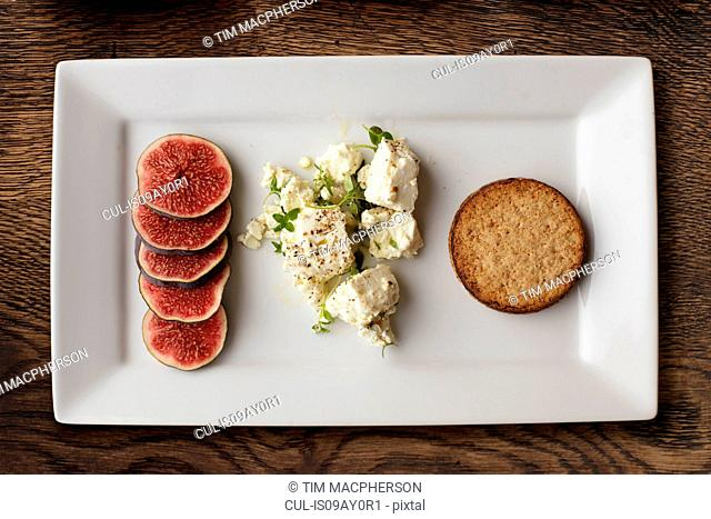 Overhead view of feta, figs and crackers on cheese board