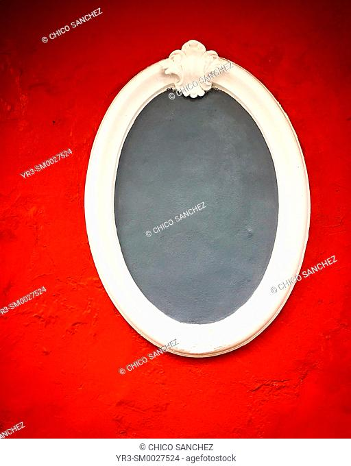 An empty grey frame in a red wall in a house in San Angel, Mexico City, Mexico